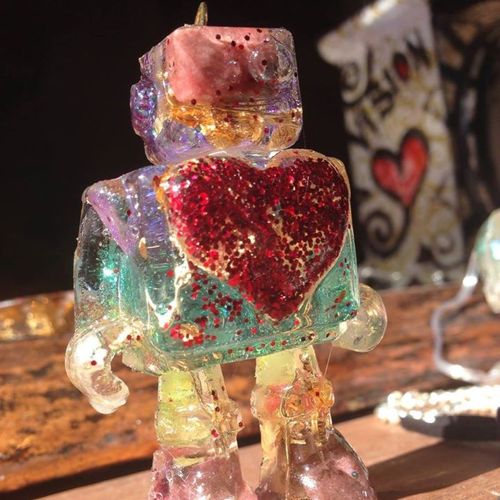 Robot product toy design made from resin and gemstones with a heart on a desk