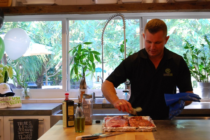 Client testing Magnefuse BBQ glove silicone product prototype on meat in a South Florida kitchen