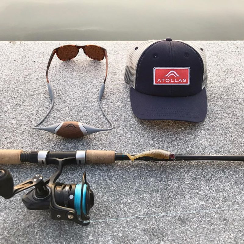 Atollas silicone sunglassess accessory product prototype attached to glasses on a south florida boardwalk with a fishing rod and hat