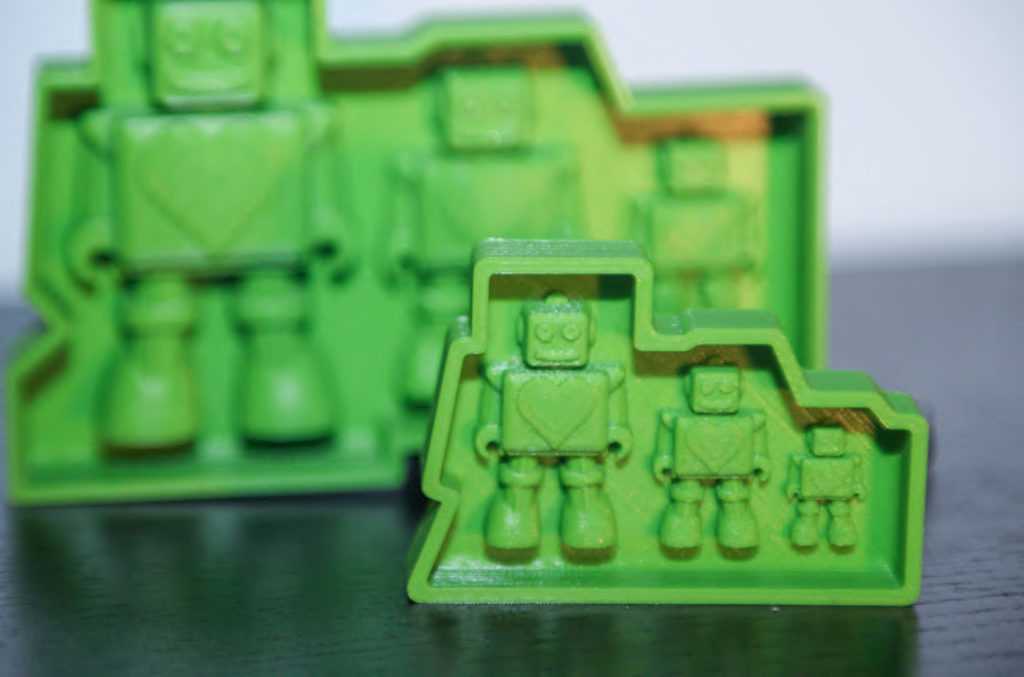 Robot toy 3D printed product prototype molds printed in green PLA plastic on a desk