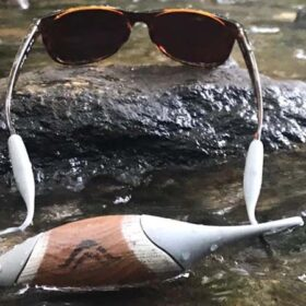 Atollas silicone sunglassess accessory product prototype attached to glasses in a south florida river with a bridge in the background